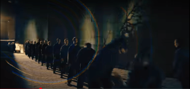A line of men in black clothing a darkened subway