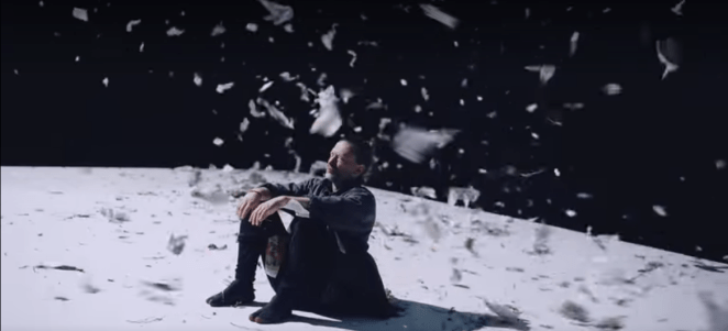 Thom Yorke sits on the ground with white paper floating around his head, in the dark