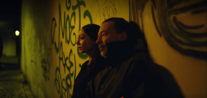 Thom Yorke and a dark haired woman look worried as they stand against a graffiti wall in a subway at night