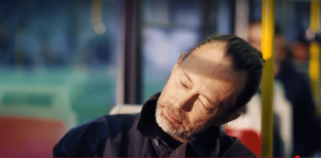 Thom Yorke rests his head and closes his eyes while travelling on the tube train