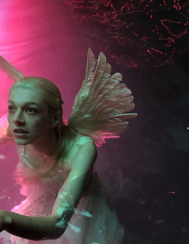 Jules swimming in a pool, dressed as Juliet from the 1996 Romeo and Juliet film.