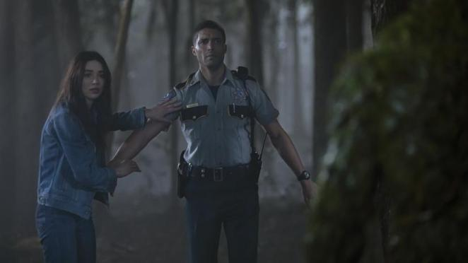 Deputy Matt Cable (Henderson Wade) with Dr. Abby Arcane (Crystal Reed) when he first meets the Swamp Thing (Derek Mears).