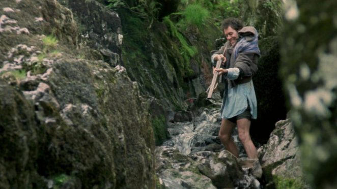 Withnail in feral mode trying to catch a fish by shooting it with a shot gun, standing in a stream