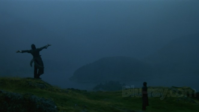 Withnail letting off some steam, arms outstretched, yelling on a hilltop