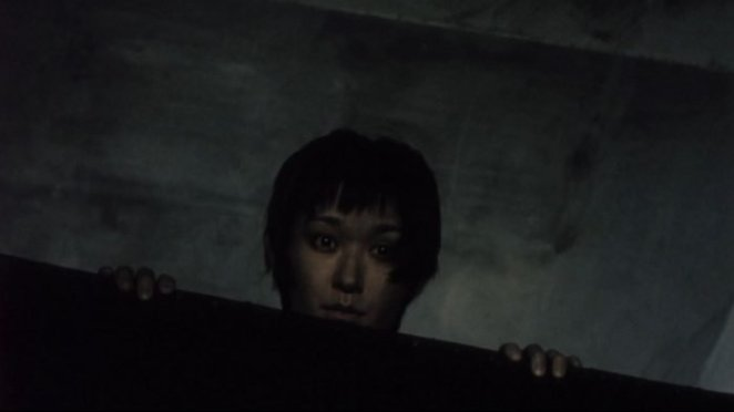 A Japanese ghost woman looks over a couch in Pulse