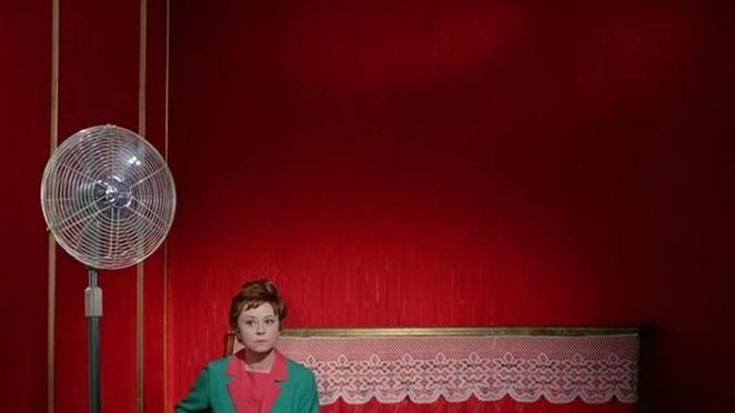Giulietta (Giulietta Masina) in the red room, waiting for the Bhisma next to an electric fan