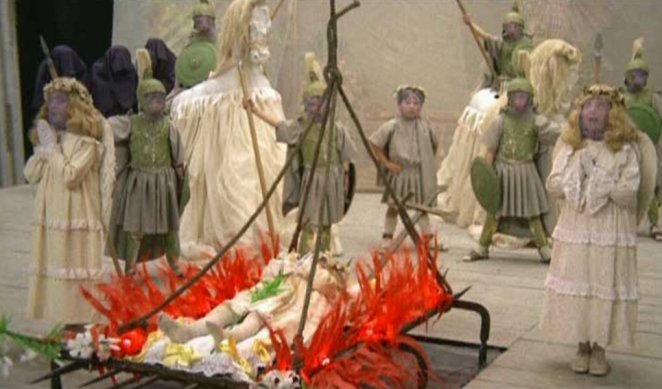 A young Giulietta is strapped to a bed of paper mache flames at her church play and surrounded by purple faced angels