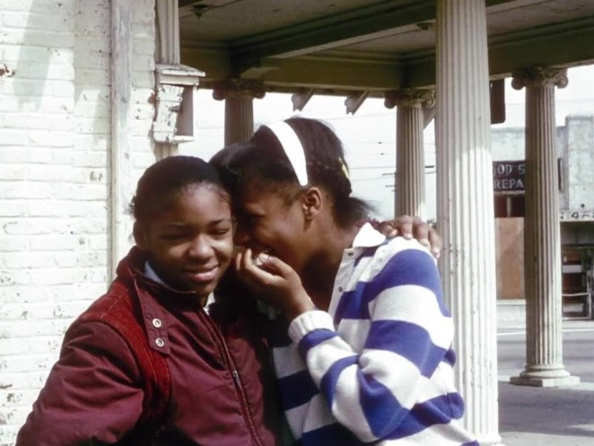 Two black girls laugh and gossip on the street