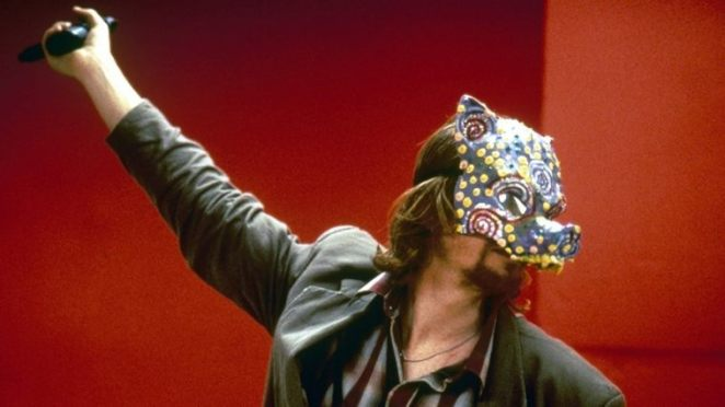 Zed (eric stoltz) wearing a painted pig mask and holding a gun up in the air against a red wall during a heist