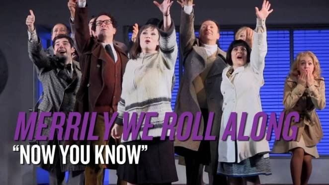 "A scene from a revival. The cast is onstage together, each with an arm raised up. The caption reads ""Now You Know"", which is the song from this scene."