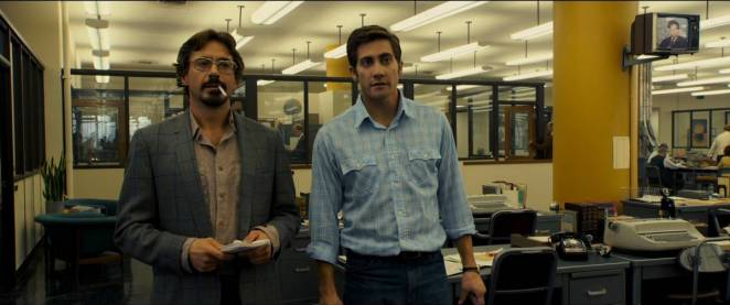 Robert Downey Jr and Jake Gyllenhaal standing against a desk in the police offices in Zodiac