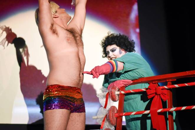 Frank-N-Furter touches Rocky's stomach, while Rocky lifts weights wearing sparkly rainbow shorts.