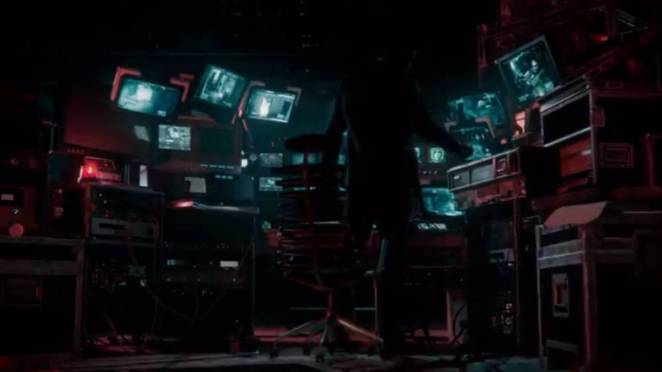 A dark figure in a room full of computers and monitoring equipment