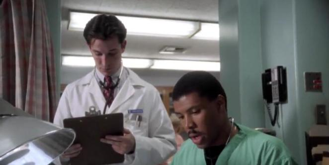 Uptight Dr. Carter tries to take notes behind Dr. Benton who is sharing information quickly.