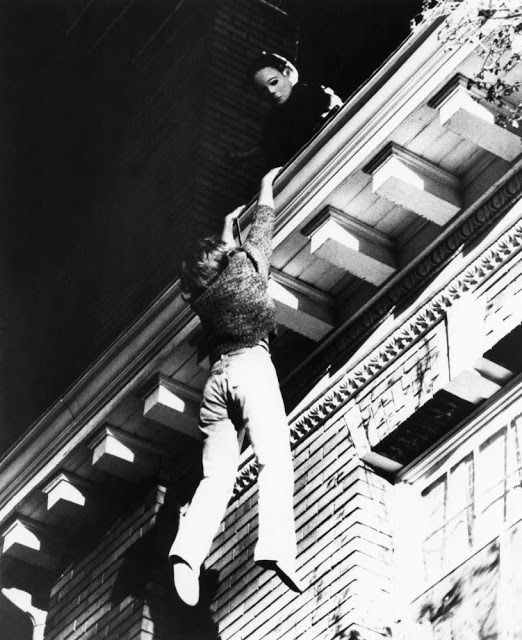 A teenage girl tightly grips a house's gutter, while a man in a mask stands above her on the roof.