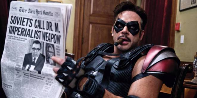 "Image from Watchmen 2009 film with Comedian in armored costume and with cigar in mouth looking away from newspaper he is holding with headline ""Soviets call Dr. M. Imperialist Weapon."""