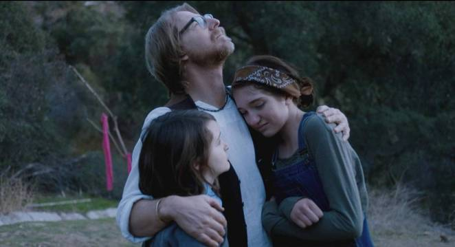 Lew Temple, Tate Birchmore, and Nicole Moorea Sherman enjoy a familial embrace in Between the Darkness (2019)