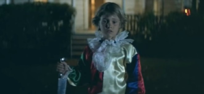 A young boy, Micheal Myers stands catatonic holding a kitchen knife in a clown suit