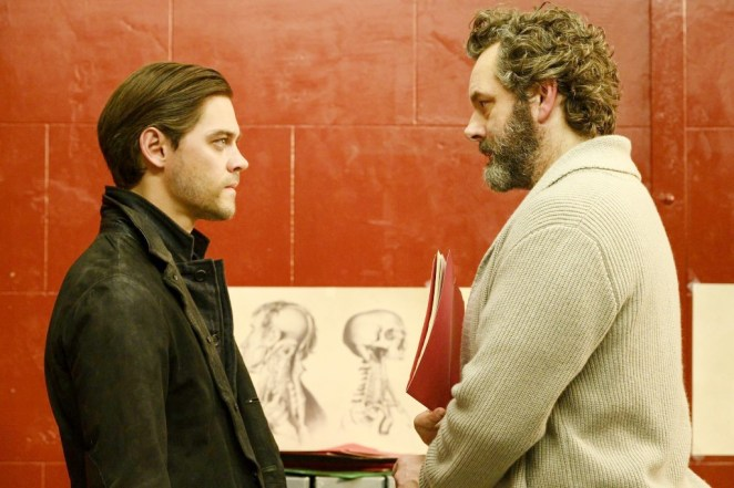Malcolm (wearing black) and Dr. Whitly (wearing a sweater and holding a folder) stare at each other with sketches in the background