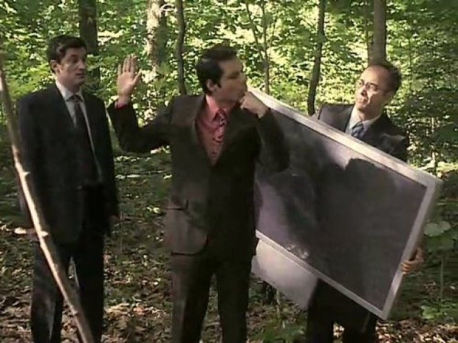 Three men in suits are lost in the woods, one of them holding a large-screen television.