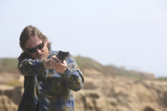 Hank, wearing sunglasses and a flannel shirt, holds up a gun
