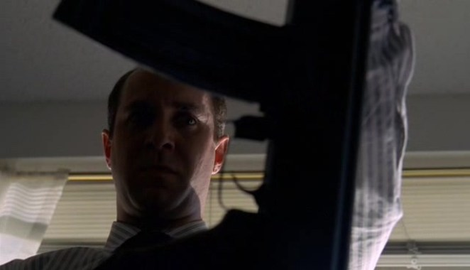 Gary Lambert is seen looking grimly at his assault rifle, with his face visible through the trigger handle of the rifle.