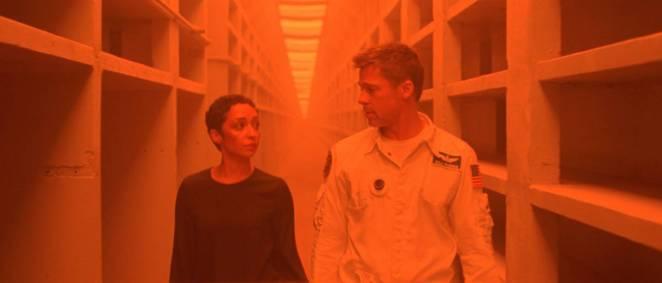 Helen Lantos and Roy McBride pass through an orange-lit hallway on subterranean Mars.