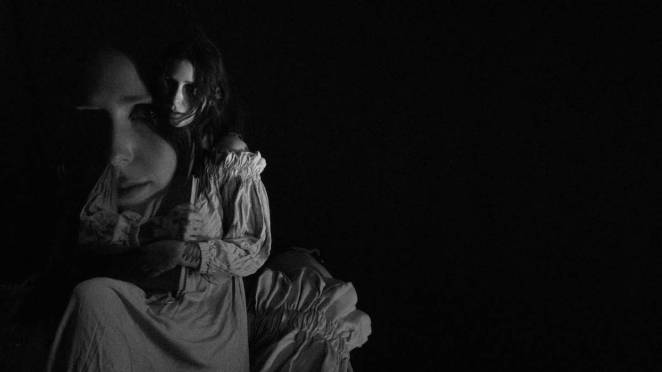 two visions of Chelsea Wolfe in a white dress in a black room