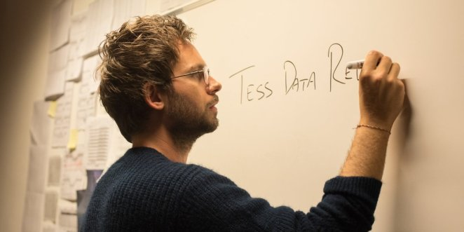 Professor Isaac Bruno (Adams) explains the TESS project on a classroom whiteboard.