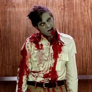 a green skinned zombie with a bloodied shirt