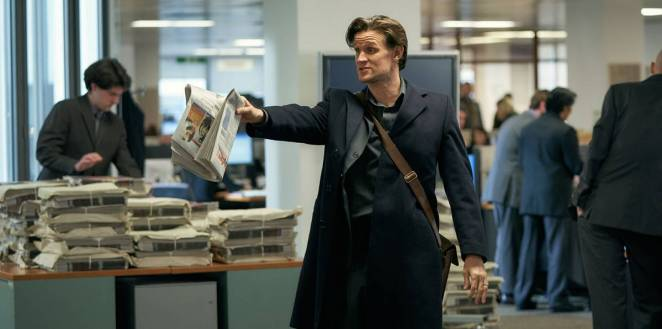 Journalist Martin Bright (Matt Smith) holds up a newspaper in the editors office