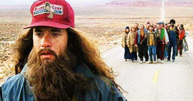 Forrest, with long hair and beard walks down a country road with a crowd following him.