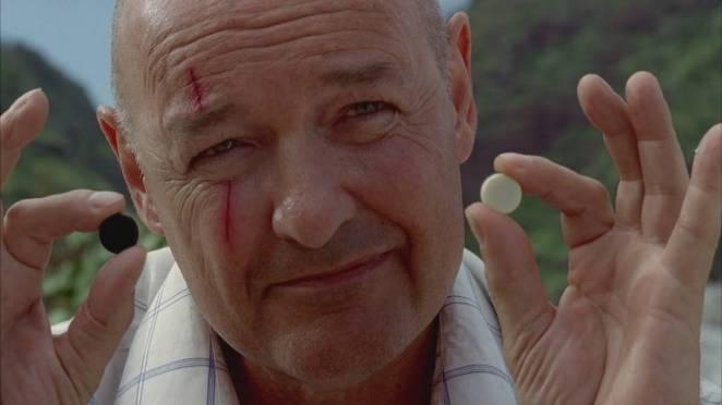 John Locke holds up one black stone and one white stone as he explains Backgammon to Walt
