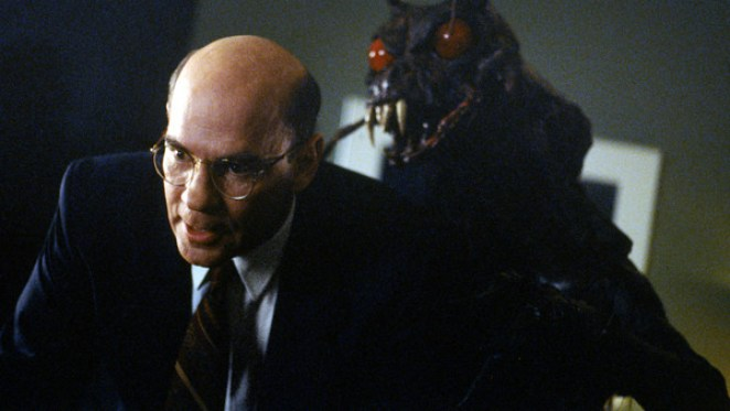The insect monster, with big red eyes and giant fangs visible, leers over Assistant Director Skinner's shoulder.