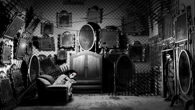 Joe stands in a room filled with mirrors while a young girl in a white dress and mask cries on a couch in the corner.