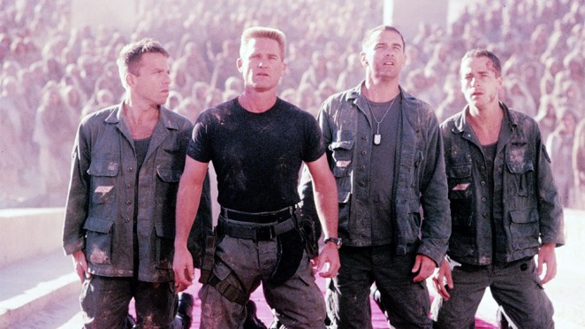 The military crew stand in judgement of the alien god Ra in Stargate.