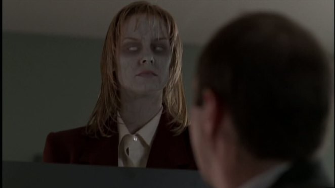 Gary's zombified coworker looks blankly over her cubicle wall at him with white eyes and pale skin.
