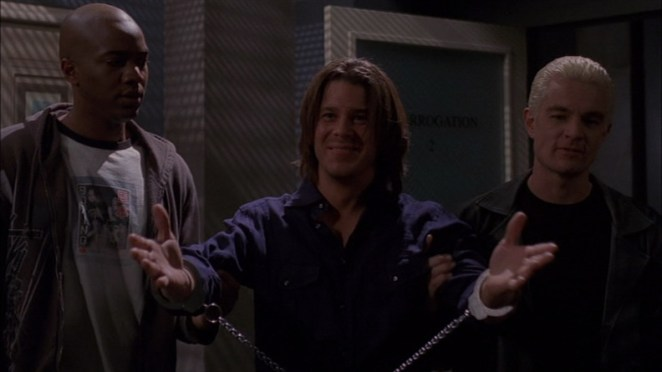 Lindsey, flanked by Gunn and Spike, holds out his handcuffed hands as if to suggest he should hug someone