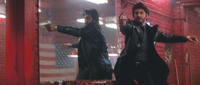 Carlito points his gun while standing next to a mirror