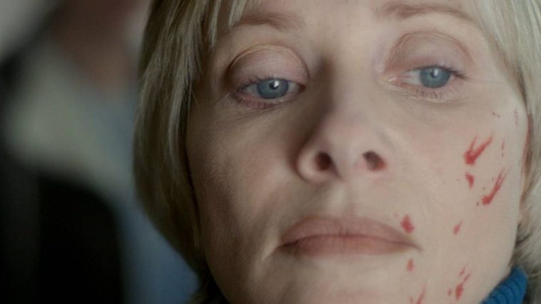 Barbara Crampton has blood on her face and stares off in the distance in We Are Still Here