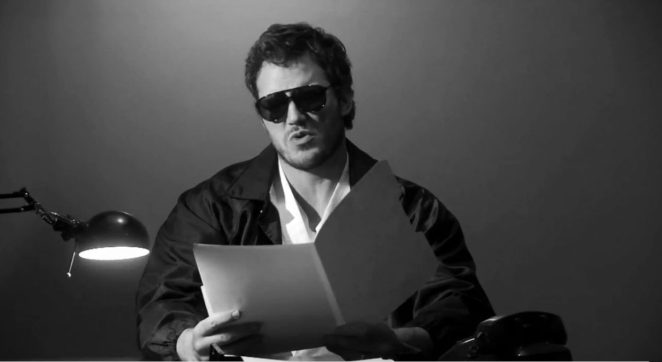 Black and white shot of Andy as Burt Macklin, FBI, sitting at a desk, wearing sunglasses and reading from a folder