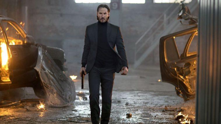 Keanu Reeves as John Wick marching through a warehouse.