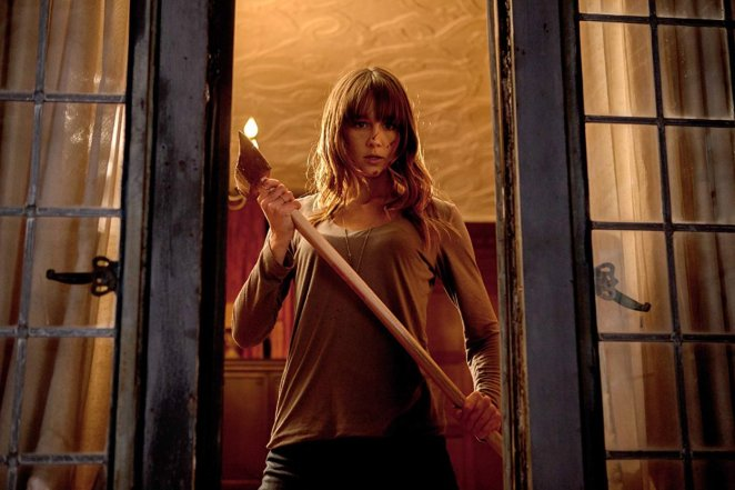 Sharni Vinston holding an axe in a doorway