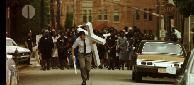 Holden walks down the streets of Atlanta carrying a cross. A large group of people are walking behind him