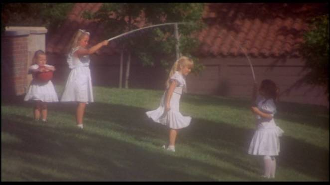 4 little girls in white dresses playing skipping rope