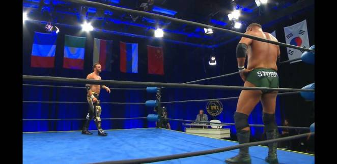 Nick Aldis and Tim Storm stand in the ring as the studio stands behind them