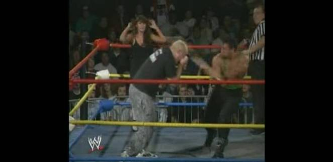 Tommy Dreamer hits The Sandman in the eyes with a cane, as Woman looks on in horror