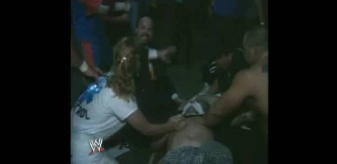 An injured Sandman lies on the ground, while Tod Gordon and others gather round him in concern
