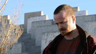 Jesse Pinkman looks down at the grouns as he stands by the side of the road