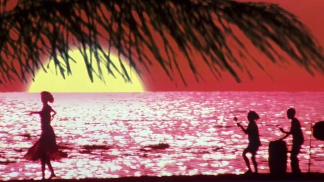 Gail dances in silhouette on a beach against a red sky with a huge yellow sun, whilst a band plays in the background